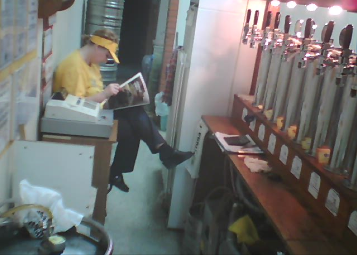 Screen capture of the web project. It's a webcam image of a bar assistant taking a break reading a magazine or newspaper.